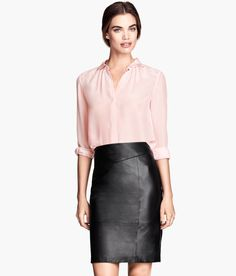 Black fitted knee-length skirt with premium-quality leather & side slit. Paired with a feminine light pink blouse. | H&M Modern Classics