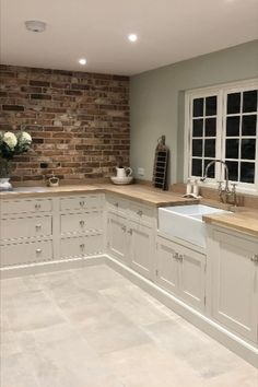 This stunning country style kitchen has hand painted cream beaded cabinets. The exposed brick wall creates a focal point and the owner has opted not to have any wall cabinets because of this. With wooden worktops, planted plinths and a huge larder it's a beautiful space to entertain in #countrykitchen #creamkitchen #handmadekitchen
