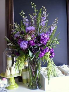 A chef's floral bouquet - centerpiece . A mix fruit, vegetables, and flowers. A vase with summer's last flowering artichokes, ornamental kale, locally grown fresh lavender and rosemary, with stock, larkspur, and amaranthuser- purple