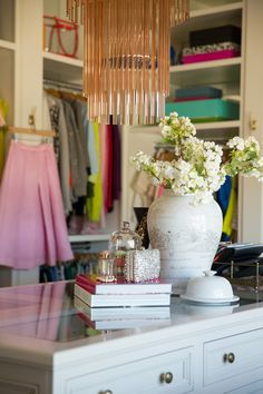 Alice Lane Home Collection | Rachel Parcell - Pink Peonies office/closet | pink chandelier, closet organization,  walk-in closet,  white ginger jar with white blossoms, fashion books, jewelry, aerin perfume, gold tray, pink skirt