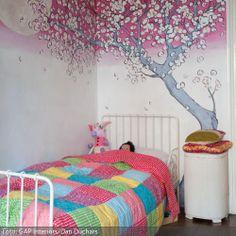 Hier werden Mädchenträume wahr. Unter den wirbelnden Kirschblüten der romantischen Wandbemalung schläft es sich zuckersüß. Die bunte Patchworkdecke bringt noch mehr Farben und Muster ins Spiel – für kleine Mädchen ein Traum. Das Kinderbett und der Nachttisch bleiben weiß und halten sich dezent im Hintergrund.
