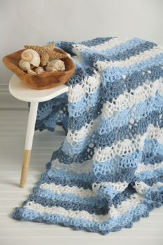 Bring the coast to you by crocheting this lacy and airy design. It's the perfect afghan for the summer months to bring some cool into the hom
