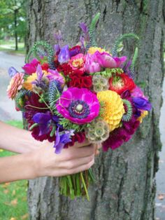 bouquet: Orange dahlia, coral zinnia, fuchsia anemone, purple sweet pea, red cockscomb, red and green ranunculus, scabiosa pods, english lavender, and veronica