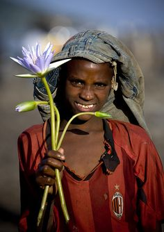 Oromo boy showing a blue water lily he picked, a flower sacred to Ancient Egyptians, as it represented a rebirth after death. It is a recurring motif in diadems worn on ladies' heads. Ethiopia by Eric Lafforgue, African Tribes, African Countries, African Men, Blog Pictures, World Pictures, Oromo People, Eric Lafforgue, Beauty Around The World, Cultural Identity