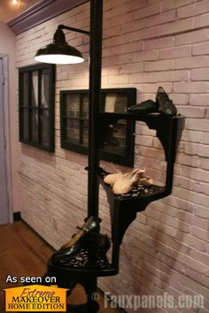 Faux brick veneer panels provide a clean backdrop for this black spiral staircase and art displays.