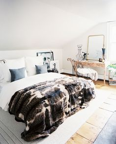 Rough luxe bedroom with fur throw, salvaged wood vanity and gray accents