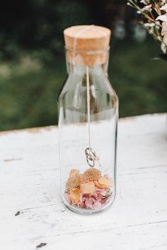 Schöne Hochzeitsfotoidee für die Trauringe: Die Trauringe hängen in einer Glasflasche mit Korkenverschluss. Am Boden der Flasche liegen Blüten und Blumenblätter in Rosa und Gelb. → Gesehen bei einer Hochzeit in der Orangerie in Köln auf frauimmer-herrewig.de | Foto: Tim Kurth | #hochzeitsfotosringe #eheringe #trauringe #hochzeitsbilderringe #hochzeitsfotosblumen #hochzeitsfotosideen Wine, Bottle, Drinks, Pink, Wedding Picture Poses, Church Weddings, Registry Office Wedding, Outside Wedding, Glass Bottles