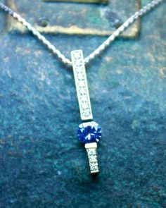 Tanzanite set in 14 karat white gold bead set with diamond accents. Hand made in my store from an original design of mine