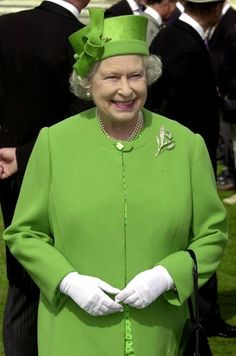 the Queen wearing a green coat, silver floral brooch, and a green knot fascinator- she's a fashion icon, definitely.