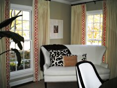 Our designer took a black and white room and added color with tangerine trim drapes