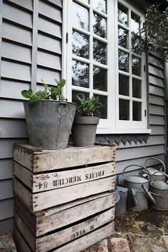 Gorgeous grey weatherboard, tin pots and watering cans, weathered boxes