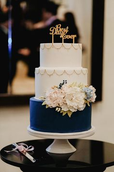 Beautiful three-tiered wedding cake in white and navy blue with gorgeous floral bloom cake toppers // How do you blend local traditions and the convenience of a modern wedding with new and exciting cultural experiences to create a wedding with a difference? We recently received an interesting answer to this conundrum in the form of Tamarind Hill and Villa Samadhi's newest garden wedding space, which will be on show at Samadhi Wedding Trail, a unique experiential wedding event on 27 August…