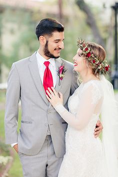 Los Angeles wedding at the Delancey Street Foundation bride lace gown with long sleeves and red and green flower headpiece with long veil and groom grey suit with white dress shirt and long red tie and red boutonniere