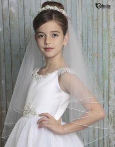 The combination of faux pearls and rhinestones on this First Communion veil are a true show stopper.  Alternating sections of pearl florets and rhinestone make for not only a stunning headpiece but a versatile one too.  And if the front weren't pretty enough, wait until you see the back with two satin ribbons and a bow with matching florette!