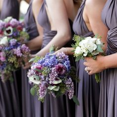 The bridal bouquet will be a loose clutch of blue purple green hydrangeas, blue delphinium, purple stock flowers, pale green succulents, purple lisianthus, lavender spray roses, and purple freesia wrapped in ivory ribbon with the stems showing