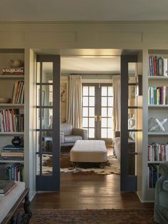Inspiration for a farmhouse enclosed living room remodel in New York with a library, gray walls and medium tone hardwood floors