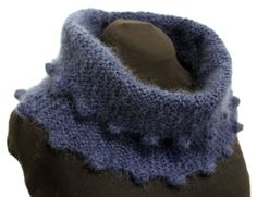 Eve Cowl By Annie Baker - MB=Make bobble: K into front, back, front, back, front and back of stitch, turn work P6, turn work K6, turn work P2Tog 3 times, turn work SL1, K2TOG, PSSO Cast on 35 stitches Rows 1-4: SL1, K to end Row 5: MB, K to end Row 6: MB, K to end Rows 7-10: SL1, K to end Repeat rows 1-10 another 16 times. Cast off. Join ends. Measures approximately 9″ x 28″ gauge = 16 stitches and 24 rows in garter stitch = 4″