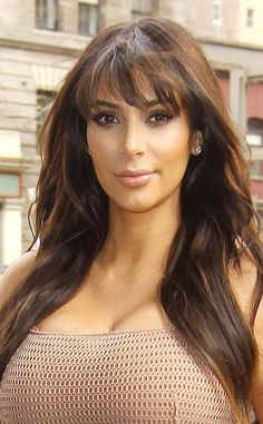 Kim Kardashian looks radiant in natural makeup and highlighted blunt bangs.