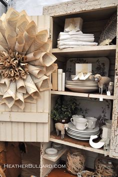 love this display and of course the paper wreath. stage pieces with frugal props stashed inside! really helps them sell!
