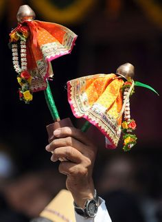 A vendor holds up miniature 'Gudis' (Lord Brahma's flag) for sale during a procession celebrating 'Gudi Padwa' in Mumbai.