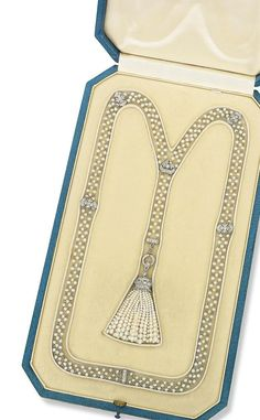 A BELLE ÉPOQUE PEARL AND DIAMOND SAUTOIR. The seed pearl tassel pendant with diamond-set pierced cap, suspended from a lattice work seed pearl chain interspersed with diamond-set panel links, 1910s, 59.0 cm, in blue leather fitted Udall & Ballou case. #BelleEpoque #sautoir