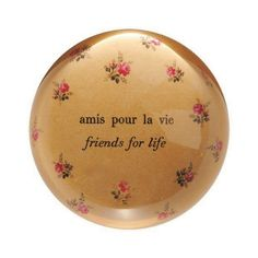 "This classic paperweight features a delicate floral background with the phrases ""amis pour la vie"" and ""friends for life"" in the middle. Dimensions: x"