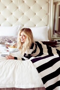 white bedding, off white tufted headboard and purple floral pillow featuring the one and only Hilary Duff
