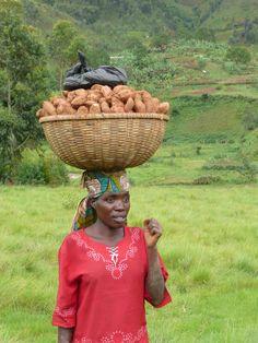 A woman walking through a mountain valley in rural Burundi