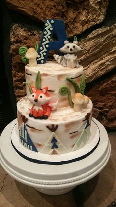 Woodland rustic baby shower cake. Woodland critters made from chocolate. Fox, racoon, and mushroom decorations.
