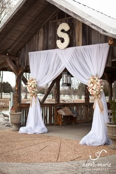 Draping entrance, tied with burlap with roses or other flowers in wedding colors.