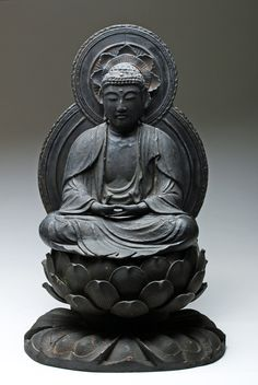 Japan, Edo Period, early 18th century (ca. 1720 CE). This is a wooden sculpture of a Buddha seated in the Dhyana mudra, the gesture of meditation, also called the full lotus position. He is covered in black lacquer over a gesso base coat. He has a red jewel embedded beneath his ushnisha (the bump on top of his head that symbolizes a part of his enlightenment) and crystal painted glass eyes. He was made out of several blocks of wood put together. The Buddha figure is seated on a 19th century…