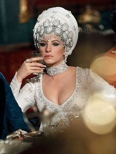 "Never-Before-Seen Photos of Barbra Streisand's Early Years in Hollywood | FEMME FATALE | The singer dazzled in a white turban as the flirtatious Melinda in 1970's On a Clear Day You Can See Forever. ""It was inspired,"" costume designer Cecil Beaton later said of the look. ""At the same time, she was totally feminine, beguiling, shamelessly sexual."""