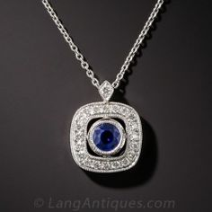 Newly made in gleaming 18K white gold, a .44 carat blueberry blue sapphire floats inside a sparkling cushion-shaped diamond frame crowned with a diamond bail. Sweet and petite - 1/2 by 3/8 inch. 16 inch chain.