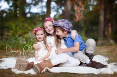 Two sisters and a brother snuggling on a blanket, autumn portrait with flowers in their hair © Dimery Photography 2013