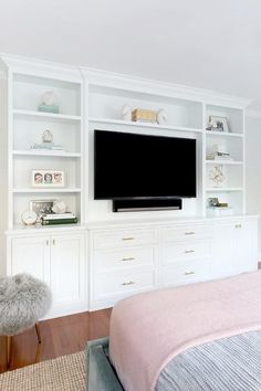 A blue velvet upholstered bed faces a built-in media center which showcases wall to wall storage space and a TV unit.