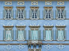 The stunning architecture and windows of an egg-shell blue building in Pisa are accentuated by the beautiful white patterns