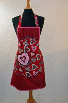 Black and red stripes play nicely off the multi colored hearts of black, white, and pink on this fun womens apron. Scalloped edges accent the bodice and the hemline with a color coordinated wave pattern embroidery. White pique lace peeks out of the inside edges of the sparkling heart pocket. The scalloped edging is accented in black metallic rick rack. Pink bias tape encases the entire apron that has been embroidered variegated waves. This apron was made from a 1943 vintage pattern and will…