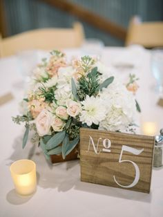 Just a hint of color works beautifully with this look for a centerpiece. Add in some tea lights and a wooden table number and voila! #weddingdecor #barn #reception Photo By - Britta Marie Photography