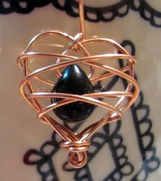 heart cage pendant. so pretty. I'd use silver colored wire with a black stone, or black colored wire and put a pearl in the middle.