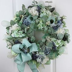 The base of this gorgeous Spring wreath is a soft green poly deco mesh with just a hint of blue. Both colours are complimented by gold highlights. The wreath is loaded with Spring & Summer flowers, lots of greenery and a large colour coordinated bow with curling tails. Buy it for