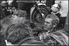 Steve McQueen seated with other riders, probably english speaking with a GB registered bike [BUE 110B] behind him ISDT 1964
