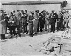 Journalists, accompanied by American military police, conduct an inspection tour of the newly liberated Buchenwald concentration camp. Apr 25, 1945.