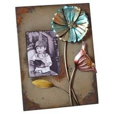 Photo frame with weathered metal flower accents.   Product: Photo frameConstruction Material: Metal and glassColor: MultiFeatures: Holds one 5 x 7 photoDimensions: 15 H x 11 W