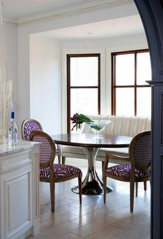 Contemporary breakfast nook bay window is filled with a cream leather curved dining banquette ...