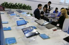 In this April 12, 2014 photo, a potential buyer, left, studies the Chinese made tablets in a booth at the Global Sources Spring China Sourcing Fair in Hong Kong. (AP Photo/Kin Cheung) ▼17Apr2014AP|China factories face new challenge as growth slows http://bigstory.ap.org/article/china-factories-face-new-challenge-growth-slows