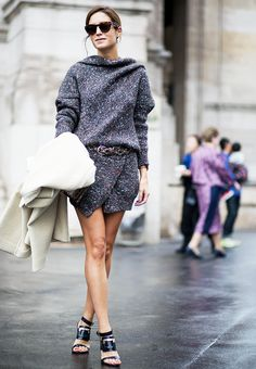 Gala Gonzalez wears a belted Stella McCartney tweed dress with strappy sandals and tortoiseshell sunglasses