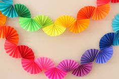 Rainbow fan garland that is so easy to make! You only need scissors, tape and paper to create this colorful DIY decoration for a rainbow theme party .