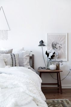 Neutral bedroom with a decorative wall hanging and simple nightstand