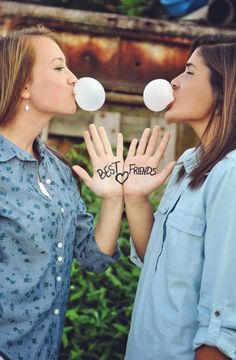 Chicas mascando chicle y mostrando sus manos con la frase best friends
