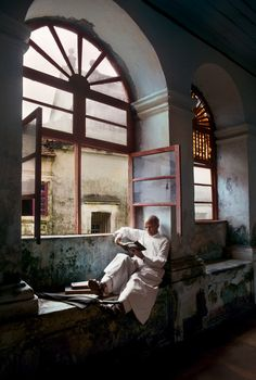Steve McCurry, INDIA. July 1978. A man sits and read by a window. (INDAI-12155)
